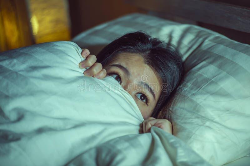 Jonge slapeloze mooie en doen schrikken Aziatische Chinese vrouw die op bed wakker bij nacht liggen die aan nachtmerrie na letten stock foto's