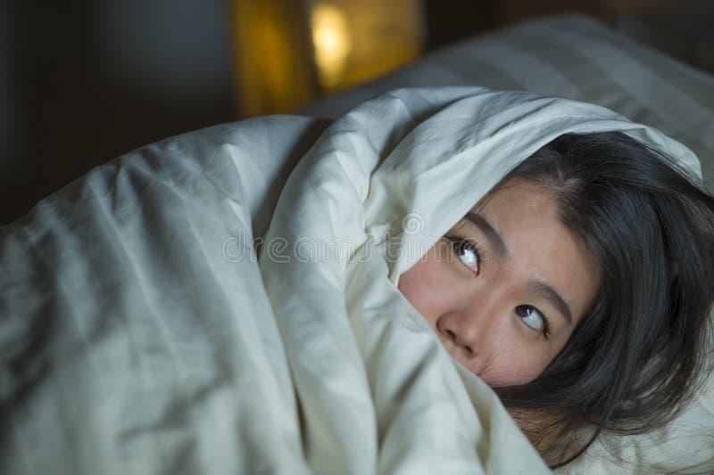 Jonge slapeloze mooie en doen schrikken Aziatische Chinese vrouw die op bed wakker bij nacht liggen die aan nachtmerrie na letten stock afbeeldingen