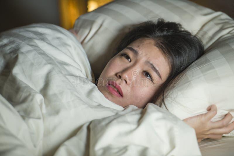 Jonge slapeloze mooie en doen schrikken Aziatische Chinese vrouw die op bed wakker bij nacht liggen die aan nachtmerrie na letten royalty-vrije stock foto