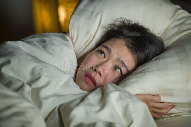 Jonge slapeloze mooie en doen schrikken Aziatische Japanse vrouw die op bed wakker bij nacht liggen die aan nachtmerrie na letten royalty-vrije stock afbeeldingen