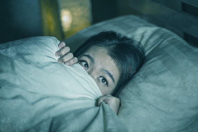 Jonge slapeloze mooie en doen schrikken Aziatische Japanse vrouw die op bed wakker bij nacht liggen die aan nachtmerrie na letten stock afbeelding