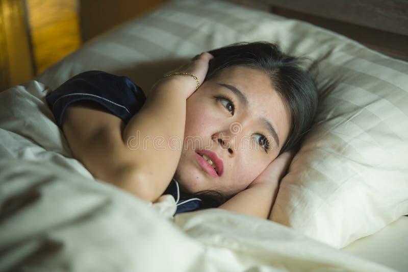 Jonge slapeloze mooie en doen schrikken Aziatische Koreaanse vrouw die op bed wakker bij nacht liggen die aan nachtmerrie na lett royalty-vrije stock afbeelding
