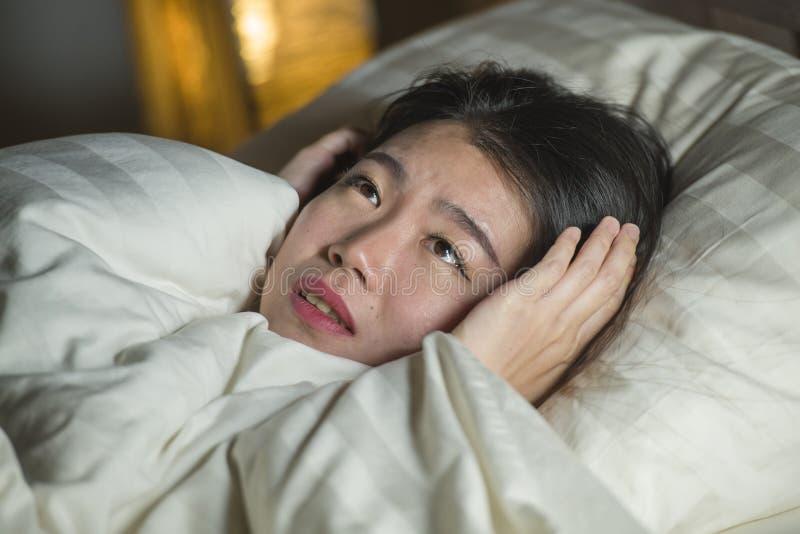 Jonge slapeloze mooie en doen schrikken Aziatische Koreaanse vrouw die op bed wakker bij nacht liggen die aan nachtmerrie na lett stock foto