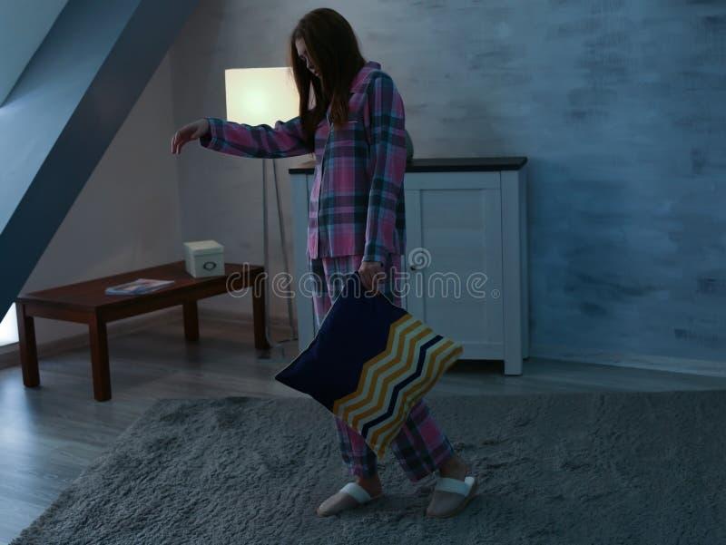 Jonge slaperige vrouw met hoofdkussen die aan somnambulisme lijden stock foto's