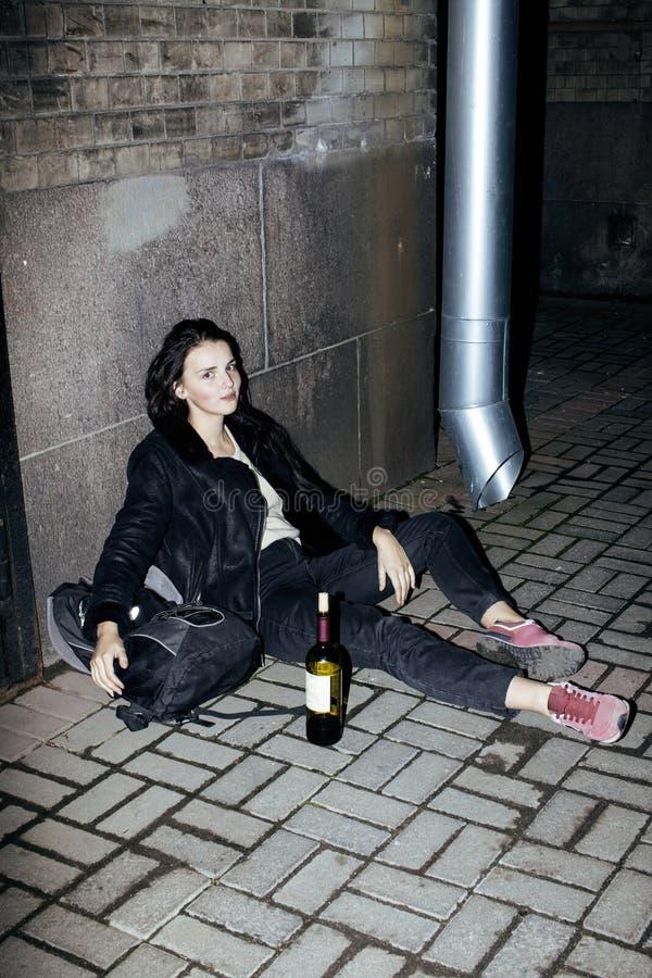 Jonge slechte tienerzitting bij vuile muur op vloer met fles van wijnstok, slechte vluchtelings alcoholische, hopeloze daklozen stock fotografie
