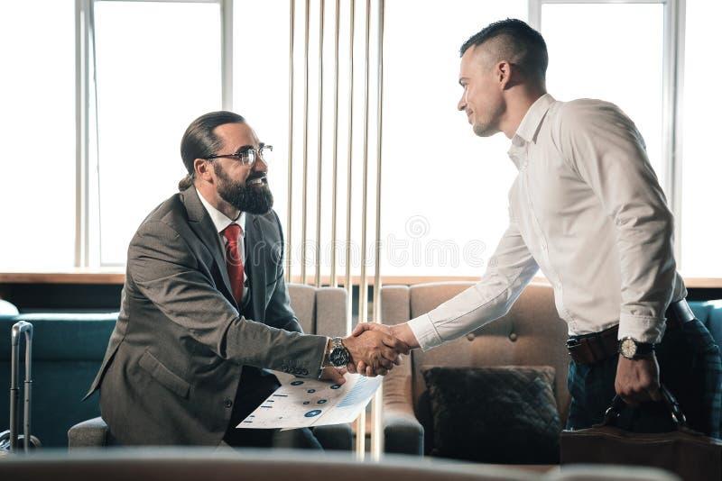 Jonge slimme zakenman het schudden hand van zijn gebaarde investeerder royalty-vrije stock foto's