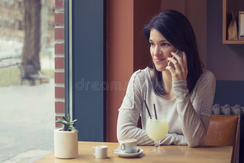 Jonge smartphone van het vrouwengebruik bij koffie royalty-vrije stock afbeelding