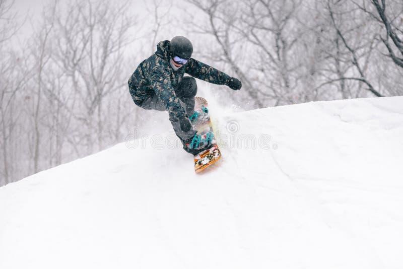 Jonge snowboarderdalingen in een halve pijp royalty-vrije stock afbeeldingen
