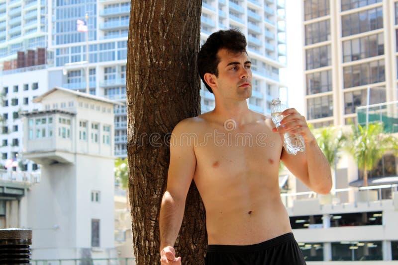 Jonge sombere mens met waterfles na looppas royalty-vrije stock foto