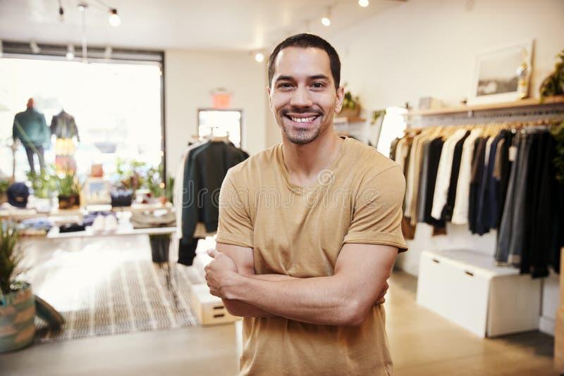 Jonge Spaanse mens die aan camera in een klerenwinkel glimlachen royalty-vrije stock foto's