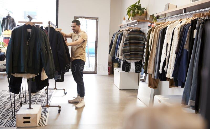 Jonge Spaanse mens die kleren in een klerenwinkel bekijken royalty-vrije stock afbeelding