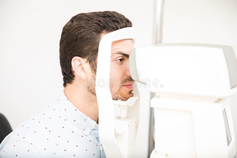 Jonge Spaanse mens die oogexamen met de optische machine van de oogtest nemen stock foto