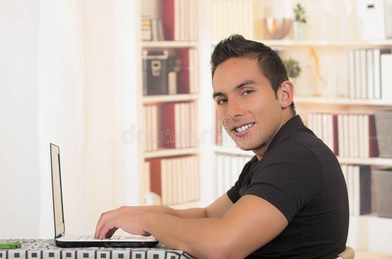 Jonge Spaanse mensenzitting bij bureau die aan witte laptop, profielhoek werken royalty-vrije stock fotografie