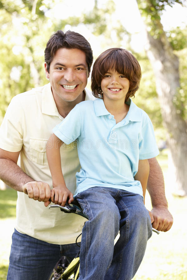 Jonge Spaanse Vader And Son Cycling in Park stock afbeeldingen