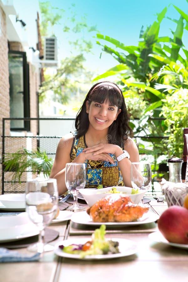 Jonge Spaanse vrouw die door de eettafel glimlachen royalty-vrije stock foto's