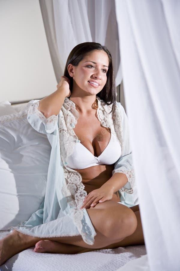 Jonge Spaanse vrouwenzitting op wit luifelbed royalty-vrije stock fotografie