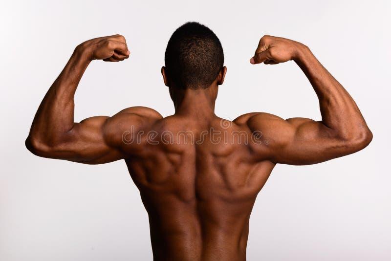 Jonge spier Afrikaanse mensen shirtless verbuiging beide wapens royalty-vrije stock foto