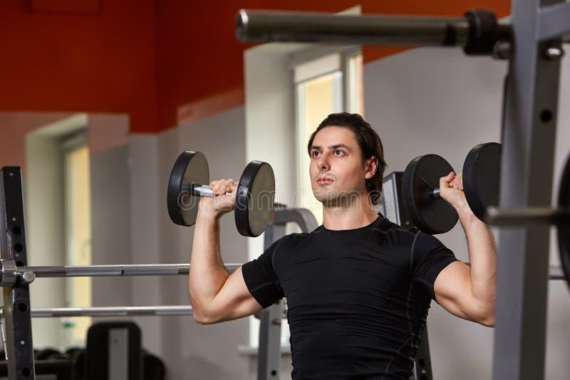 Jonge spier gebouwde atleet in zwarte sportwear zitting op een gewichtheffenmachine en het opheffen van twee domoren royalty-vrije stock foto