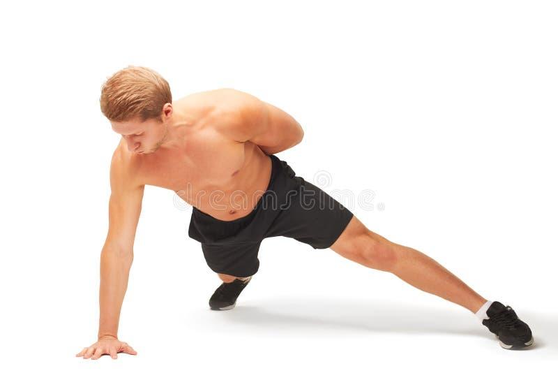Jonge spier knappe shirtless sportman die opdrukoefeningen op één wapen doen stock foto's