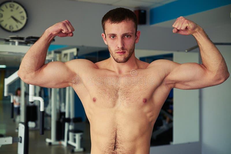 Jonge spiermens die van hem tonen goed - opgeleid lichaam in gymnastiek stock afbeeldingen