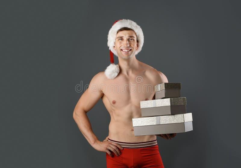 Jonge spiermens in Kerstmanhoed met giftdozen stock foto's