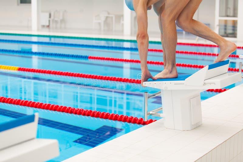 Jonge spierzwemmer in lage positie inzake startblok een zwembad royalty-vrije stock foto
