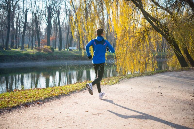 Jonge Sportenmens die in het Park in Koud Sunny Autumn Morning lopen Gezond levensstijl en sportconcept royalty-vrije stock foto