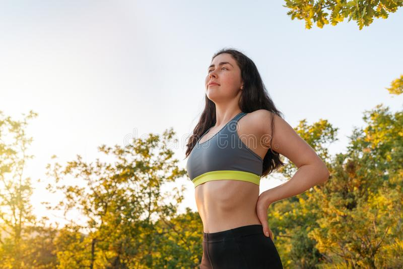 Jonge sportenvrouw belast met opwarming vóór sporten Het concept sport, fitness en gezonde levensstijl stock foto's