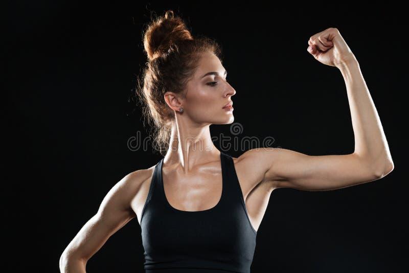 Jonge sportenvrouw die haar bicepsen tonen stock fotografie