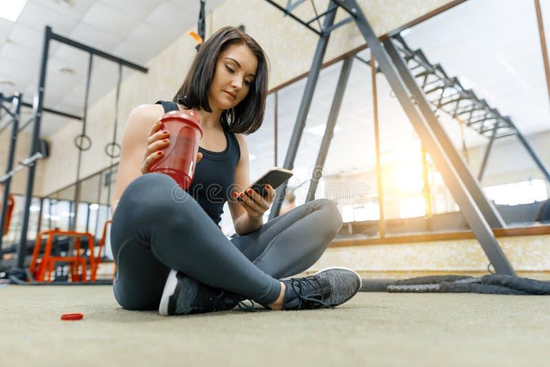 Jonge sportenvrouw die op de vloer na oefeningen in gymnastiek rusten, smartphone van de drinkwaterlezing fitness, sport, die opl royalty-vrije stock fotografie
