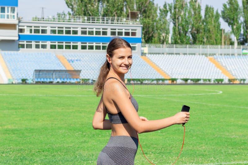 Jonge sportenvrouw die in stadion lopen en mobiele telefoon het luisteren muziek gebruiken Sporten en gezond concept royalty-vrije stock foto