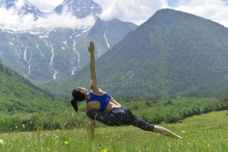 Jonge sportenvrouw die yoga op het groene gras in de zomer doen royalty-vrije stock afbeeldingen