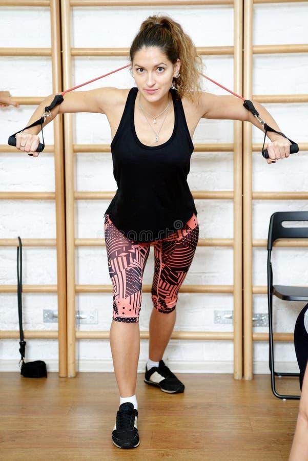 Jonge sportenvrouw in gymnastiek die materiaal met behulp van trx stock foto's
