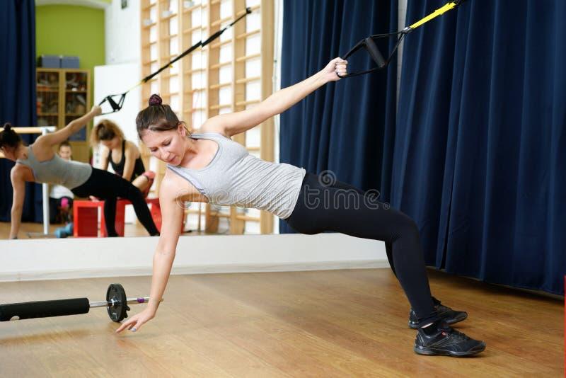 Jonge sportenvrouw in gymnastiek die materiaal met behulp van trx stock foto