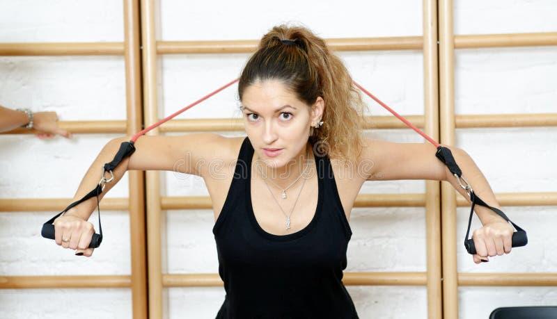 Jonge sportenvrouw in gymnastiek die materiaal met behulp van trx royalty-vrije stock fotografie