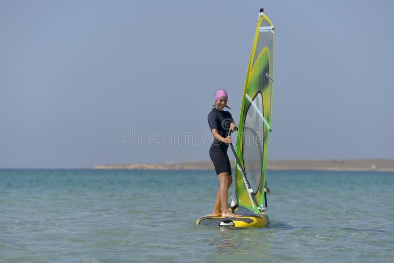 Jonge sportenvrouw Windsurfing op zee op een Zonnige dag royalty-vrije stock foto's