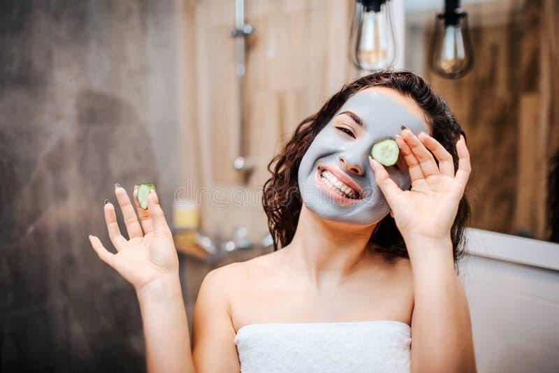 Jonge sportieve donker-haired mooie vrouw die de routine van de ochtendavond doen bij spiegel Het gelukkige positieve model kijkt royalty-vrije stock afbeeldingen