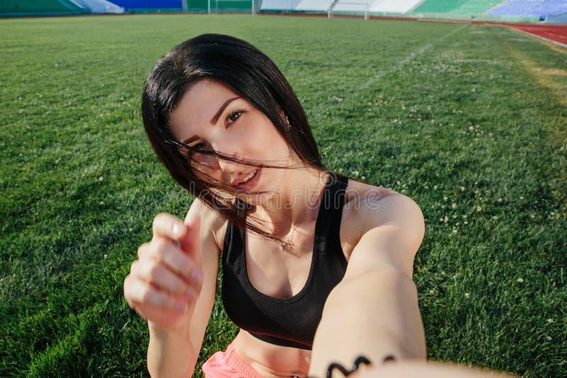 Jonge sportieve donkerbruine vrouw in meisje in sportenkleren die selfie, glimlachgezicht dicht omhoog op gras doen Meisje na een royalty-vrije stock fotografie