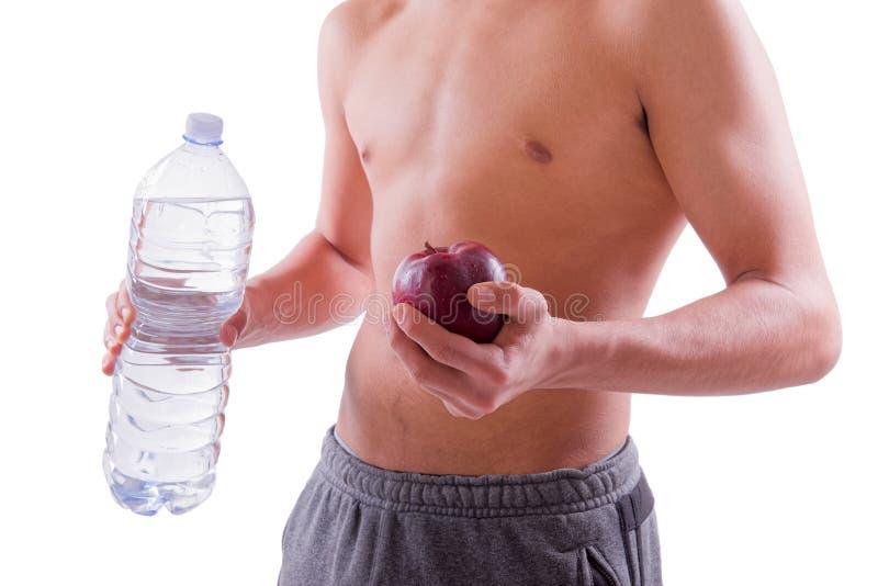 Jonge sportieve mens die rode appel en fles water houden stock foto