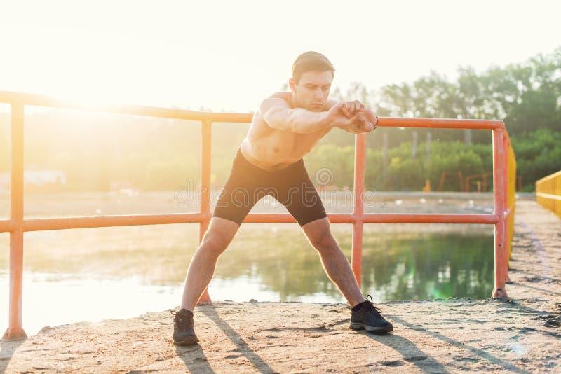 Jonge sportieve mens die vooruit en uitrekkende oefening buigen doen royalty-vrije stock foto