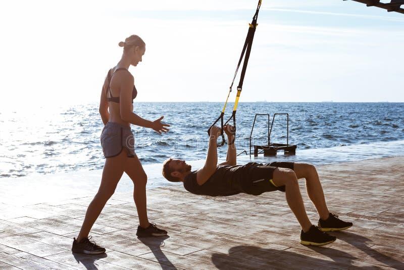 Jonge sportieve mensen die met trx dichtbij overzees in de ochtend opleiden stock afbeelding