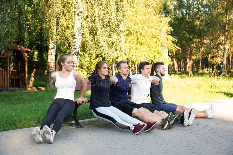 Jonge sportieve mensen die oefeningen op bank in openlucht doen stock foto's