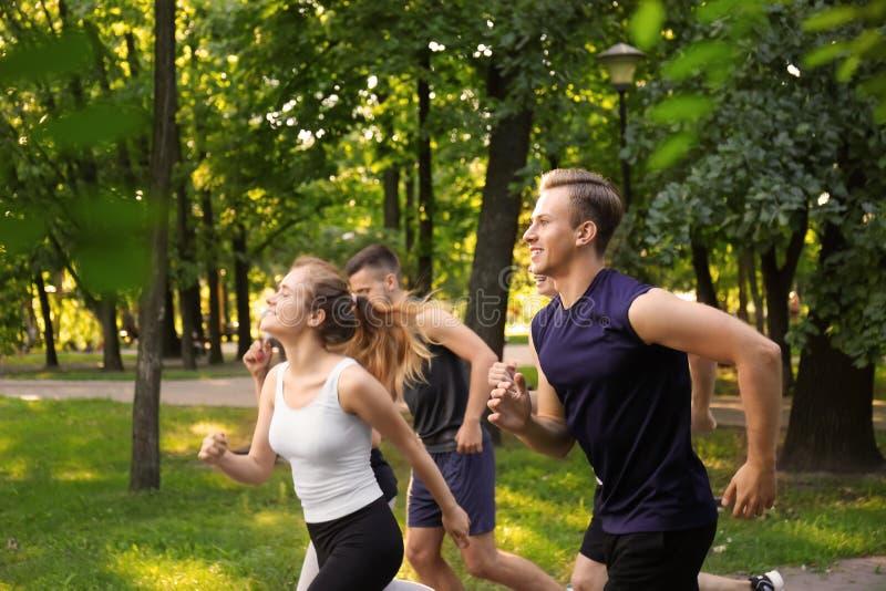 Jonge sportieve mensen die in openlucht lopen stock afbeeldingen