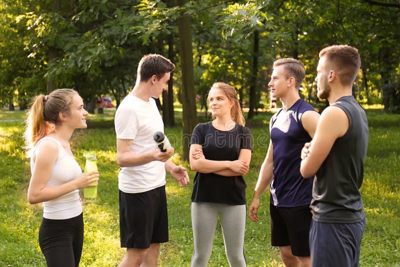 Jonge sportieve mensen die rust na in openlucht opleiding hebben royalty-vrije stock afbeelding