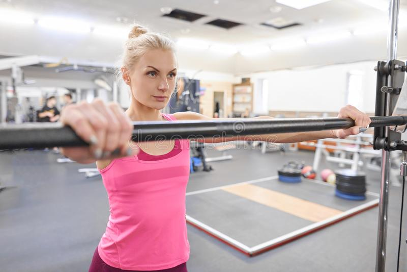 Jonge sportieve mooie blonde vrouw in de gymnastiek De fitness van de mensenschoonheid concept van de sport het gezonde levenssti royalty-vrije stock afbeeldingen