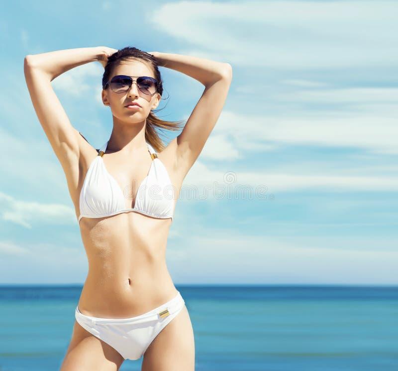 Jonge, sportieve, mooie en sexy vrouw in zwempak het stellen op a stock afbeelding
