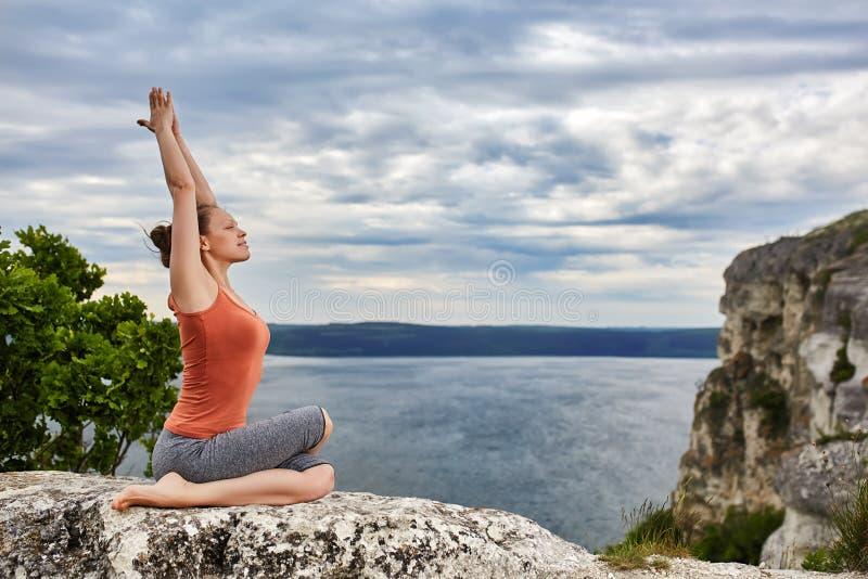 Jonge sportieve vrouw asanas van de opleidingsyoga op rots boven mooie rivier royalty-vrije stock foto's