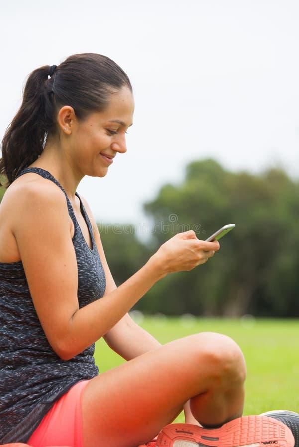 Jonge sportieve vrouw bij het slimme telefoon texting royalty-vrije stock foto's