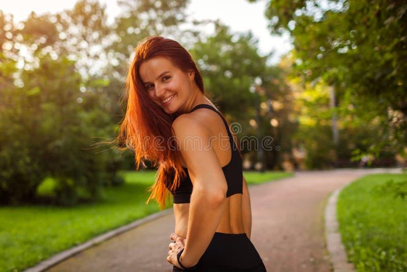 Jonge sportieve vrouw die camera na training in de zomerpark bekijken sportkleding Sterke vrouw die rust hebben royalty-vrije stock foto's
