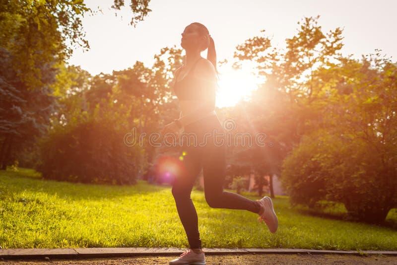 Jonge sportieve vrouw die in de zomerpark lopen Sportvrouwjogging Opleiding royalty-vrije stock fotografie